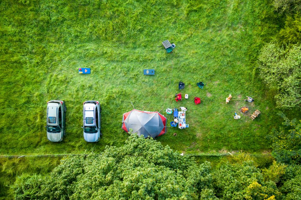 Overland Camping Shelter Options: Hipcamp campers hanging out tent camping in farm fields on the weekend. (Photo by: Edwin Remsberg/VW PICS/Universal Images Group via Getty Images)