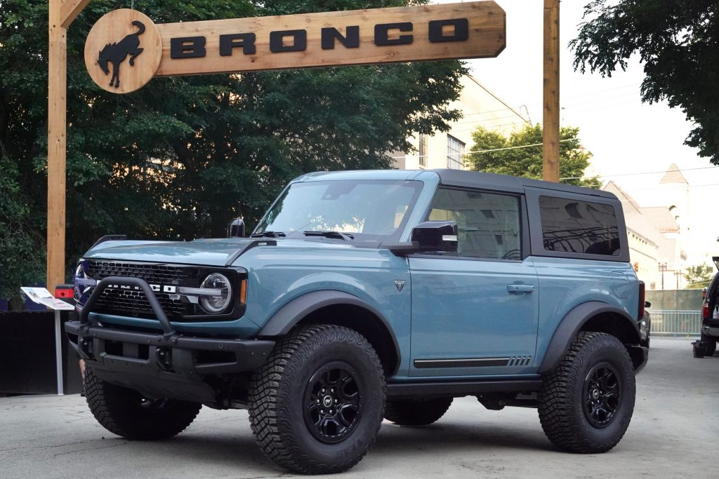 A 2022 Bronco sits under a banner bearing its name at the Chicago Auto Show