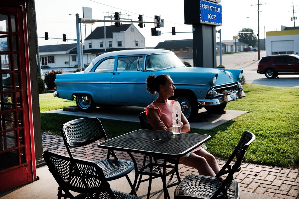 A woman sits on a patio with a 50's-era car in the background