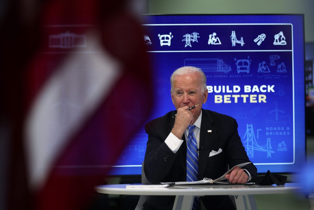 Joe Biden sits at a table while promoting his new infrastructure bill