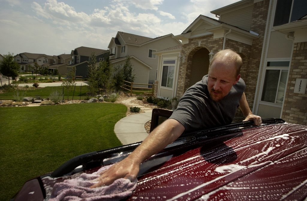 Man Washes His SUV in the driveway at home