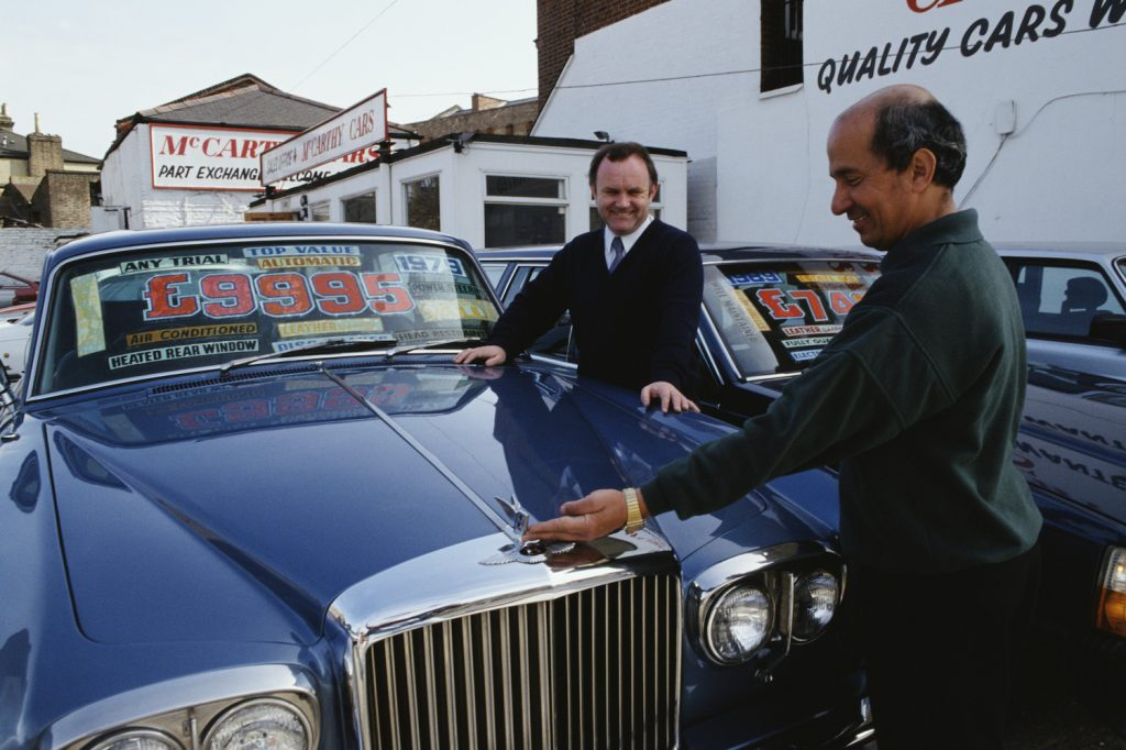 Second hand car salesman Vincent McCann admires a 1979 Bentley with a customer, UK, 1992. (Photo by Tom Stoddart Archive/Getty Images) Do open recalls change a cars trade-in value?