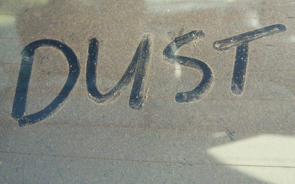 the word dust spelled out by rubbing a finger on a dirty windshield