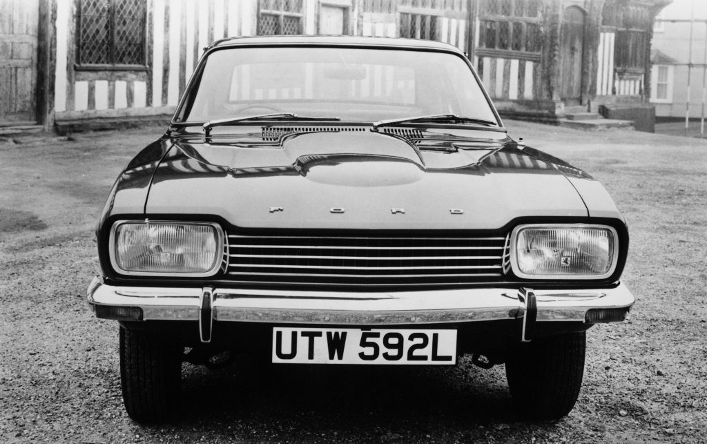 The front end of an old 1973 Ford Capri sedan in black and white