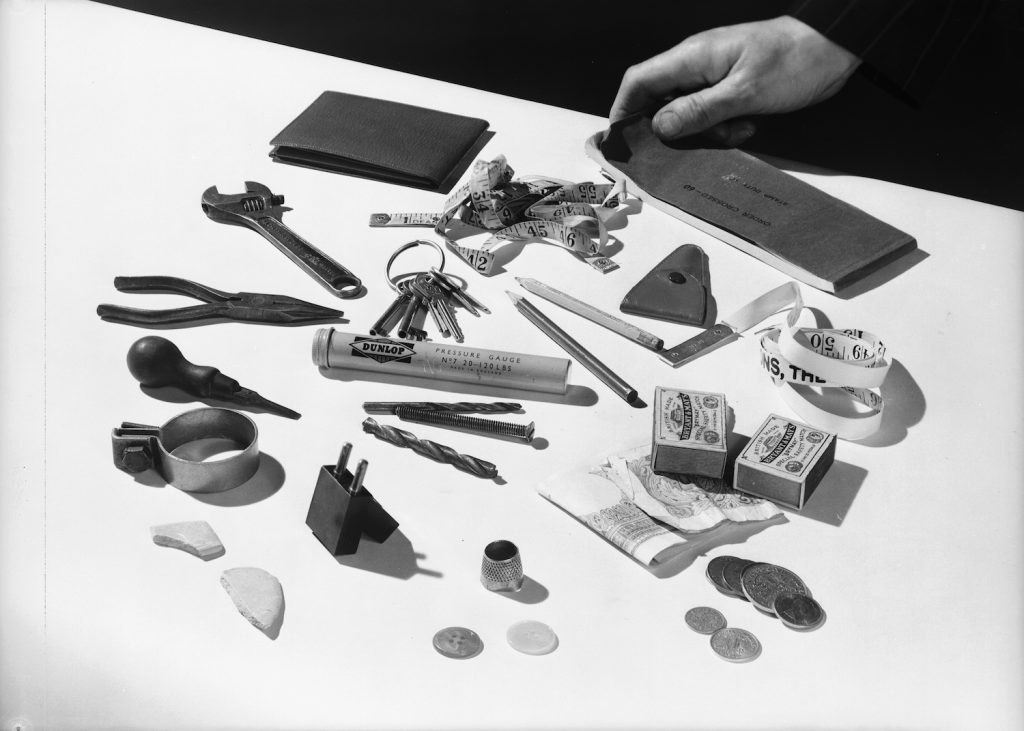 28th May 1954:  A collection of random objects, including a tape measure, a Dunlop pressure gauge, a thimble, and an assortment of tools, keys, buttons, money and matchboxes.  (Photo by Chaloner Woods/Getty Images). Some random items from our do it yourself car hacks.
