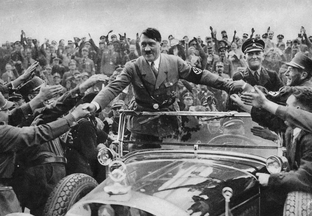 Adolf Hitler rides in a Mercedes-Benz convertible while greeting supporters in Nuremberg 1933