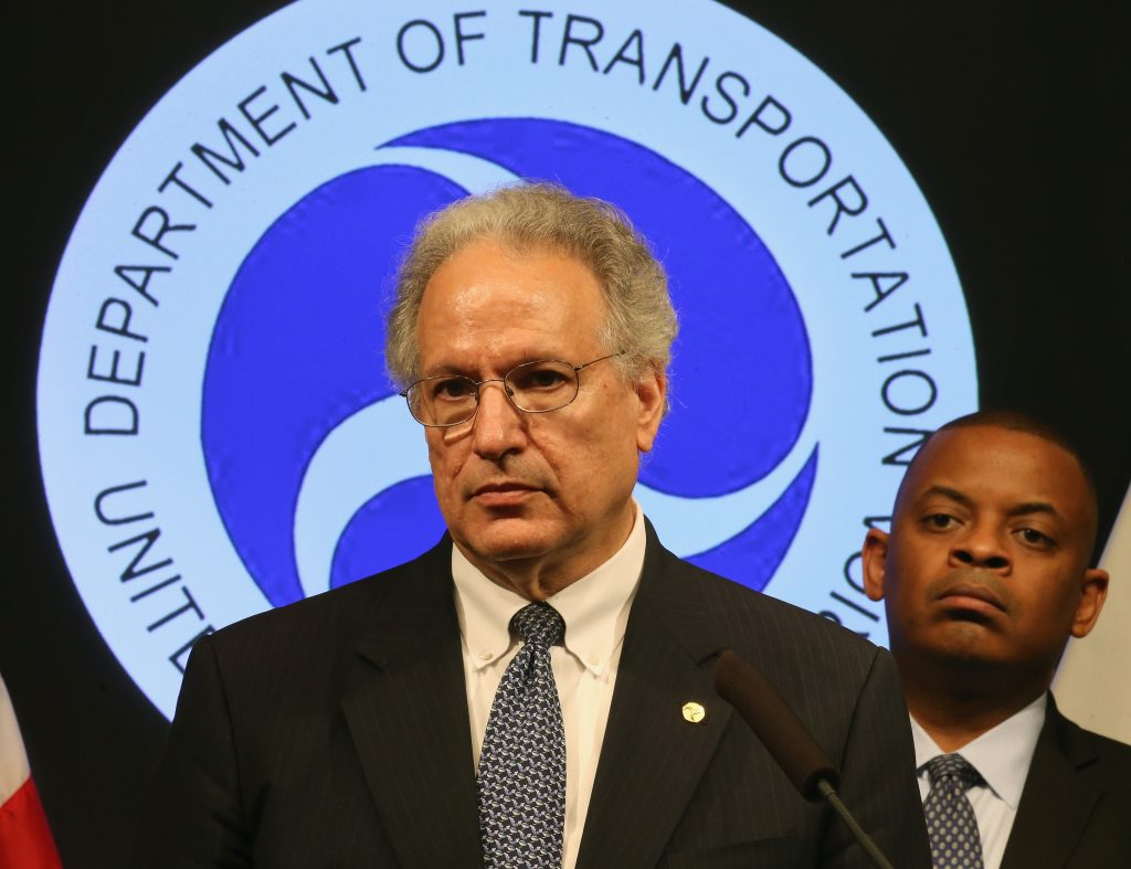 NHSTA admin Mark Rosekind at a conference, with the agency's logo behind him