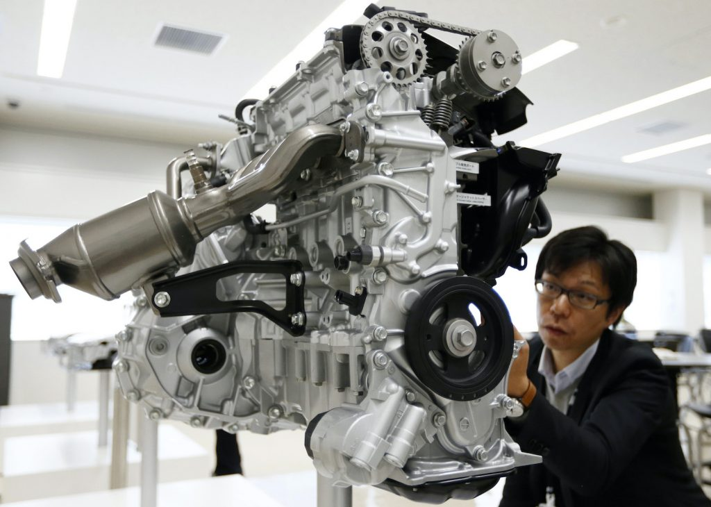 An employee looks at the engine for the Toyota Motor Corp. fourth-generation Prius hybrid vehicles ahead of a test drive at Fuji Speedway on November 12, 2015 in Oyama, Shizuoka prefecture, Japan. Tomohiro Ohsumi/Getty Images. Learn to decode your toyota engine name with our Toyota engine family chart and engine feature table.