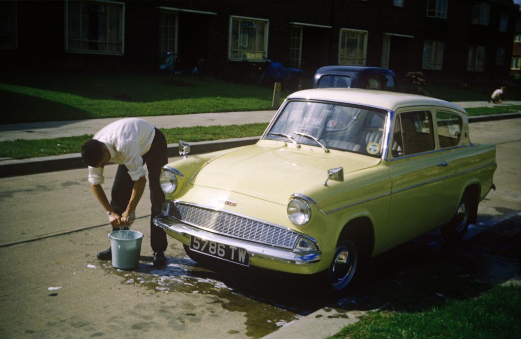 Man Washes His Classic Ford Anglia Car