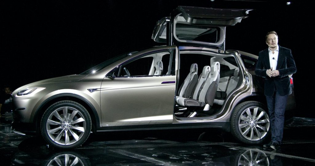 A gray Tesla Model X and Elon Musk at a press event. The Model X is among the best electric SUVs of 2021.