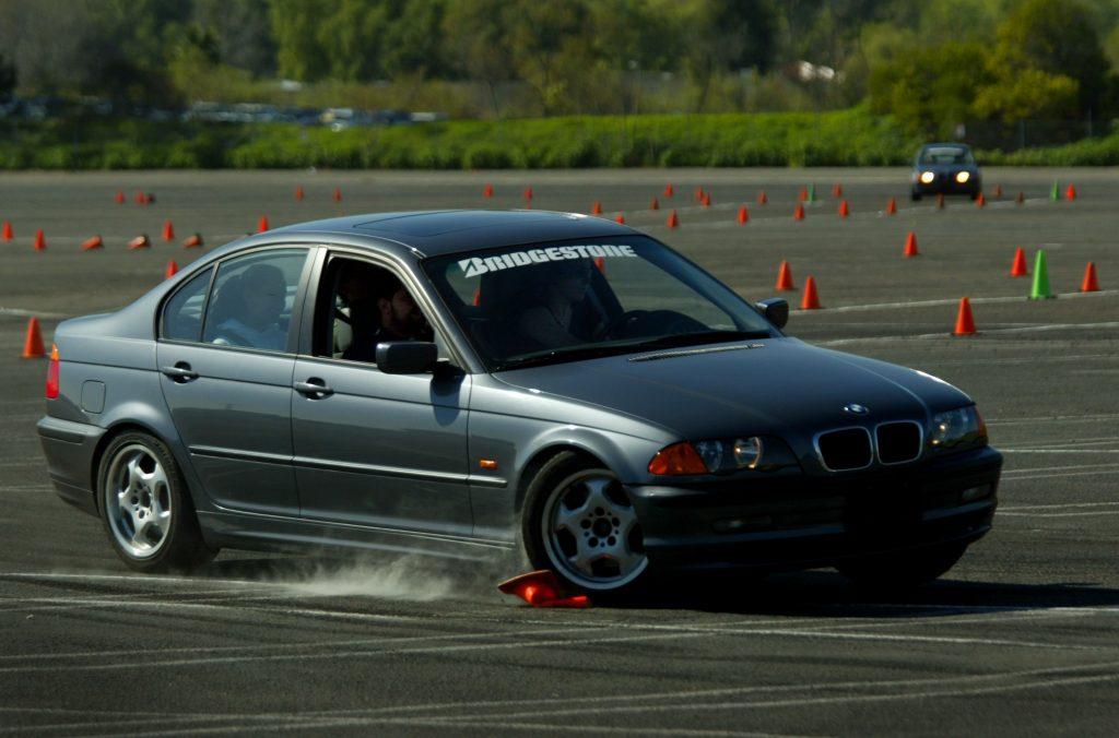 A BMW runs over a cone at an autocross course