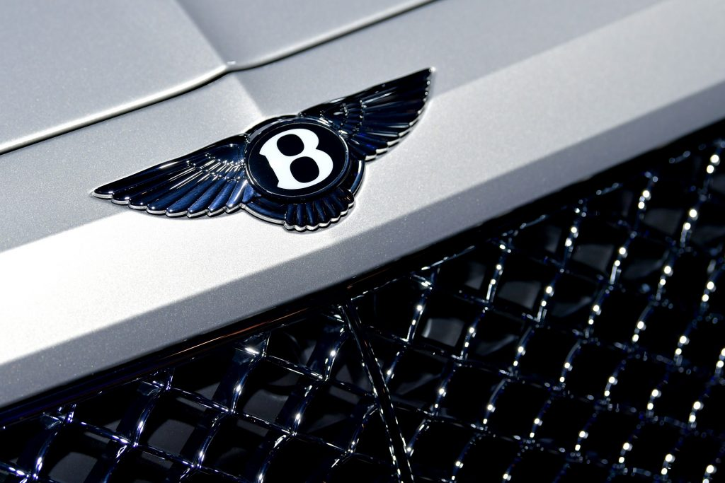 """The flying """"B"""" logo on the hood of a white Bentayga"""