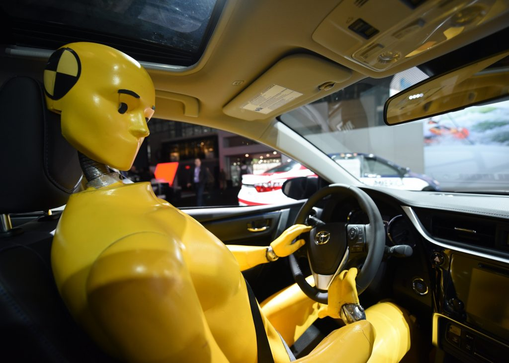 A crash test dummy at the wheel of a Toyota Corolla