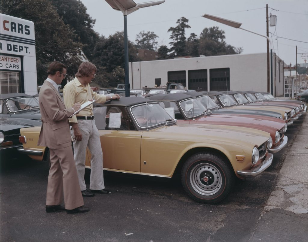 A second hand car salesman and a man admiring brand new Triumph TR2s in the UK. Photo by Lambert/Getty Images. Do open recalls change a cars trade-in value.