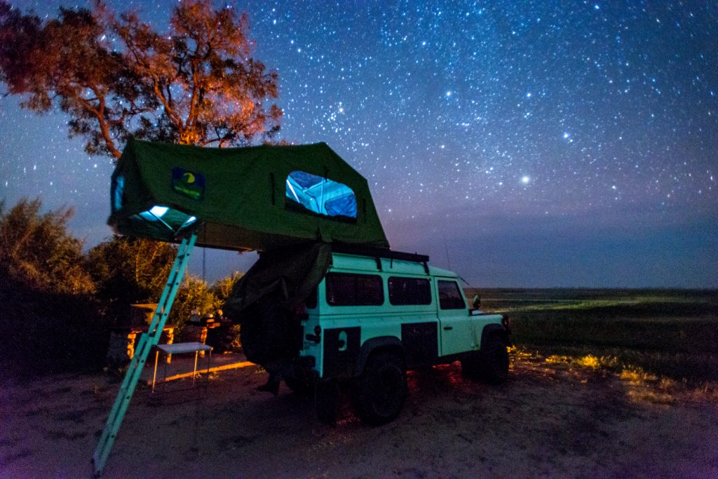 Botswana, Africa- Land Rover parked with a pop up tent on its roof under the night sky. (Photo by: Edwin Remsburg/VW Pics via Getty Images) One of the 5 Best Rooftop Tents For Overlanding -- According to Popular Mechanics