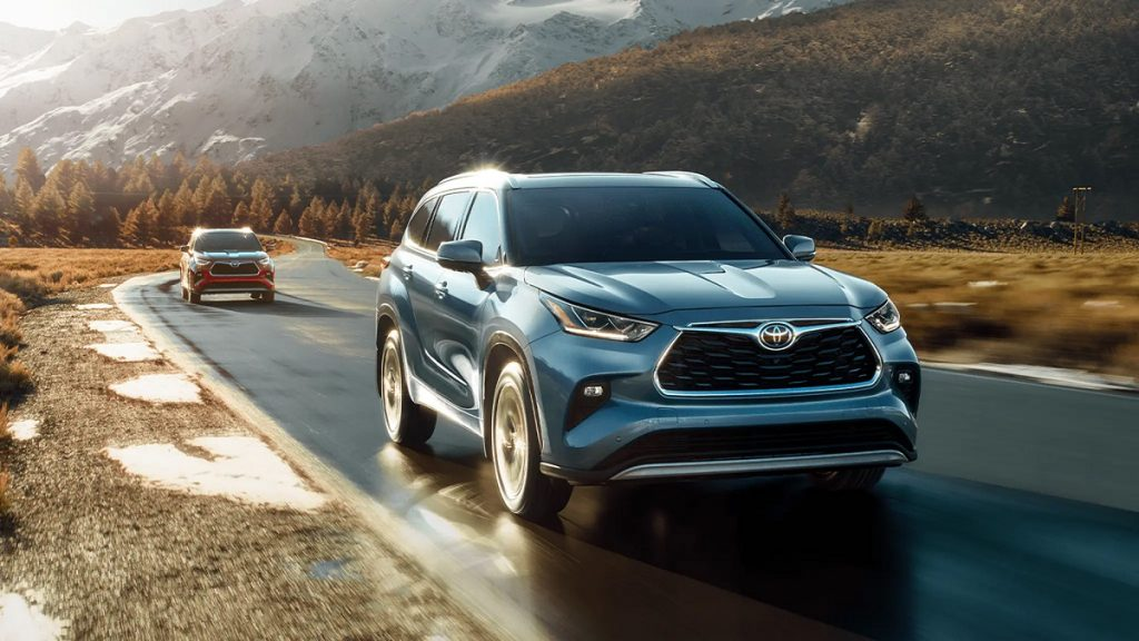 A blue 2021 Toyota Highlander driving with mountains in the background.