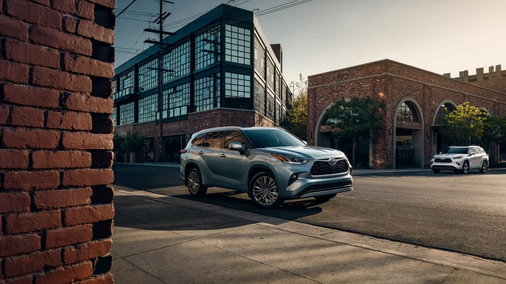 A silver 2021 Toyota Highlander driving down a street surrounded by brick buildings.