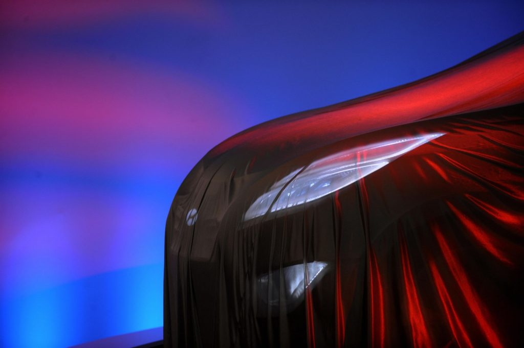 A headlight covered in a veil that gives off a red glow with a blue and pink background.