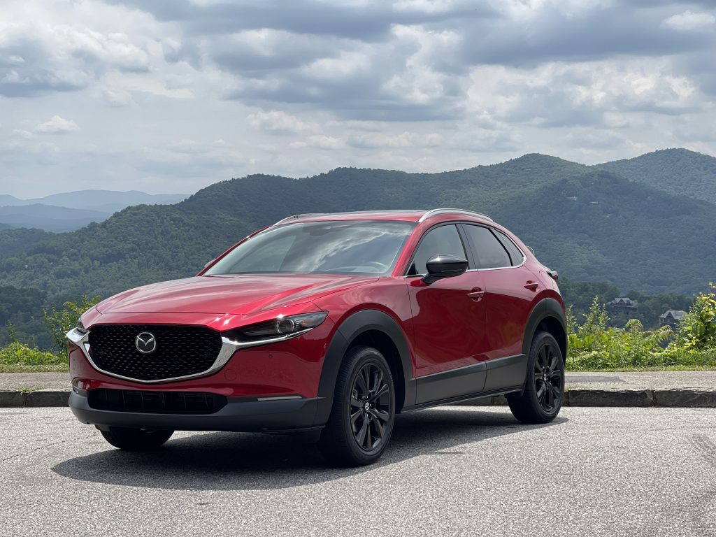 A red 2021 Mazda CX-30 turbo parked in front of a mountain view