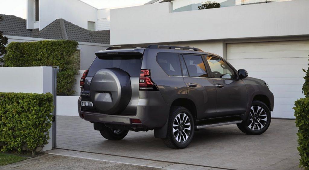 a Land Cruiser Prado in a modern driveway