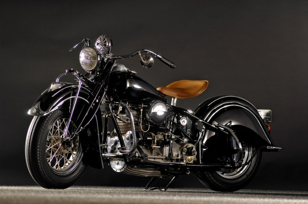 An old black Indian Motorcycle with a tan seat against a dark grey background.