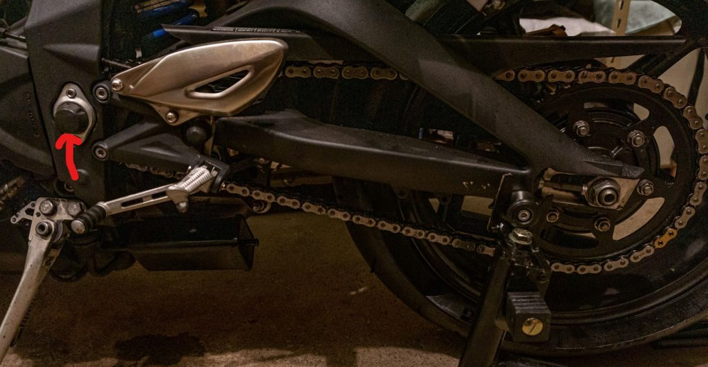 A 2012 Triumph Street Triple R motorcycle's chain and rear sprocket with its swingarm pivot indicated by a red arrow