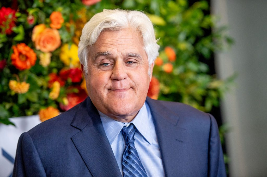 Jay Leno wearing a blue suit with a light blue shirt and a dark stripped blue tie in front of a flowered background.