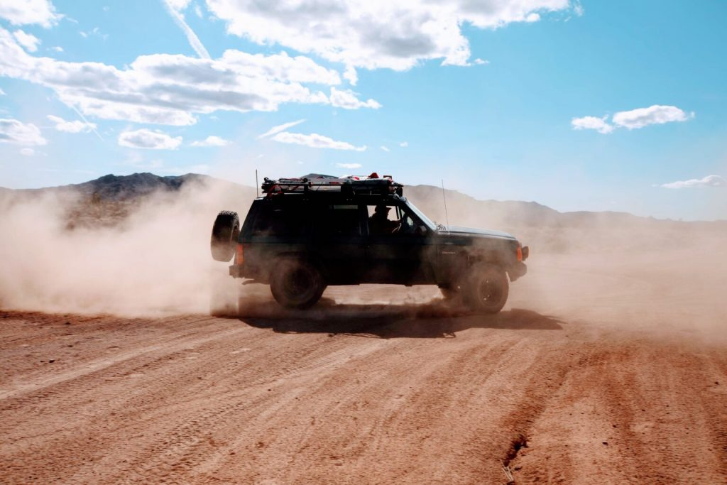 Classic 90s off-roader, Jeep Cherokee kicking up dust in the desert