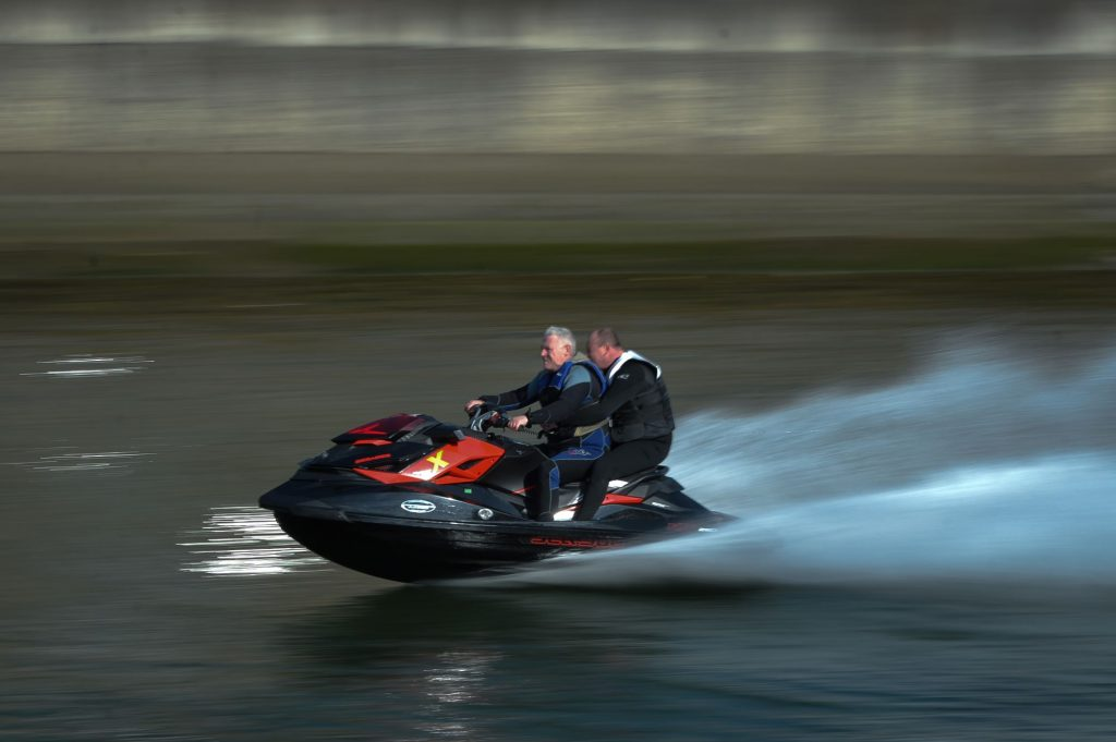 2 men riding on a black and red jet ski in a large body of water wearing black jackets and pants.