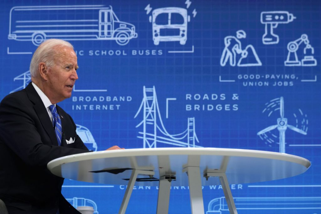 Joe Biden sitting at a white table in a chair dressed in a suit and tie in front of a blue background with engineering sketches of various things, such as road and bridges, wind turbines, etc.
