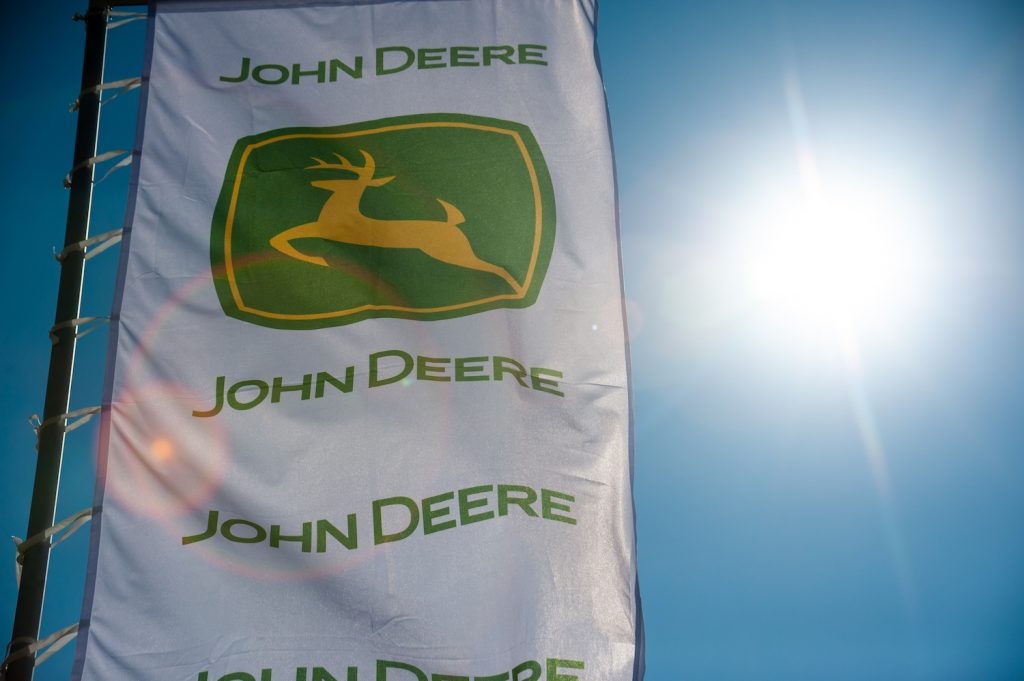 The John Deere logo on a white flag with the sun shining through it, Consumer Reports recommends several of the best John Deere zero-turn mowers