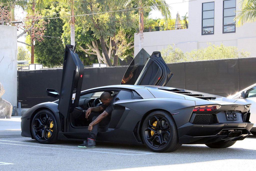 Kayne West exiting an exotic luxury car model in Los Angeles, California