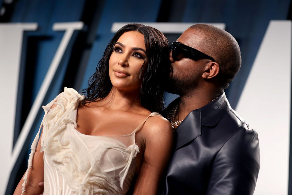 Kim Kardashian West is dressed in an ivory dress with Kanye West in a black shiny suit jacket in front of a blue, black and white background.