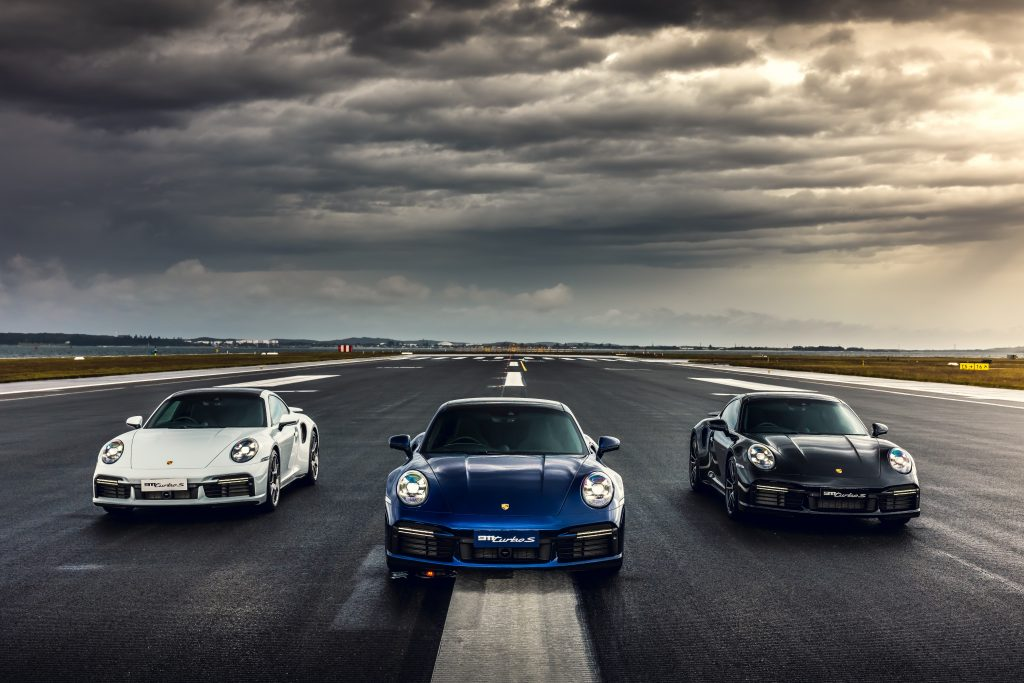 A lineup of three Porsche 911 Turbo models on a runway