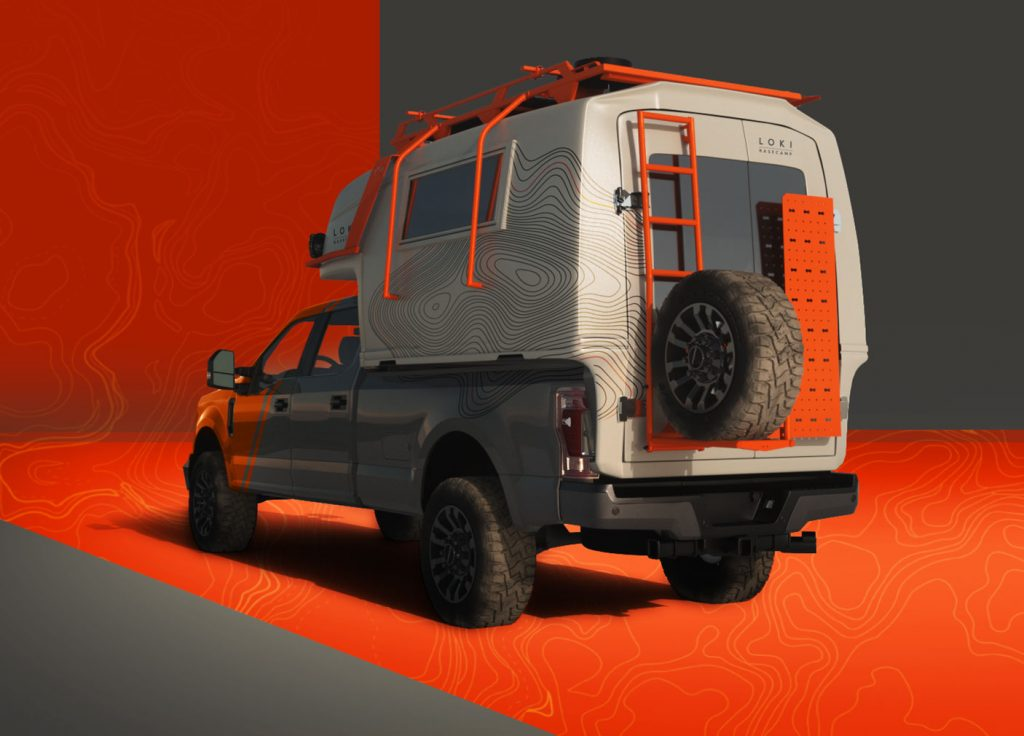 The rear of the Icarus camper, with a tire mounted on the back and orange railing covering the exterior