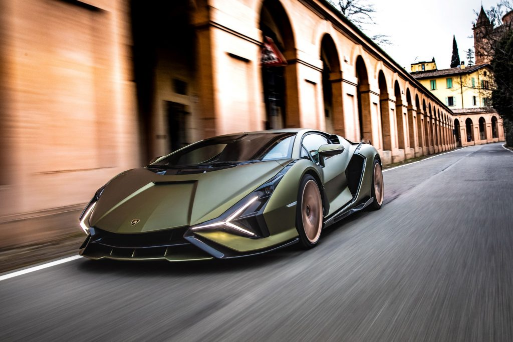 The front 3/4 view of the matte-green Lamborghini Sian driving through the Bologna streets