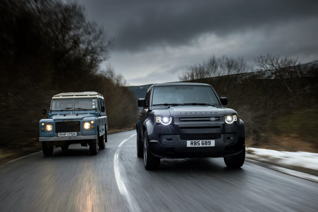 A 1977 Land Rover Defender Series III Stage One V8 and a 2021 Land Rover Defender 90 V8 travel side-by-side on a wet road