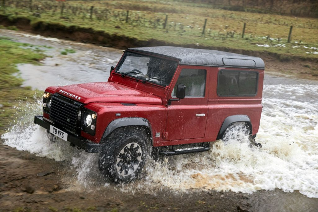 A Land Rover Defender V8 Heritage model driving through a shallow river