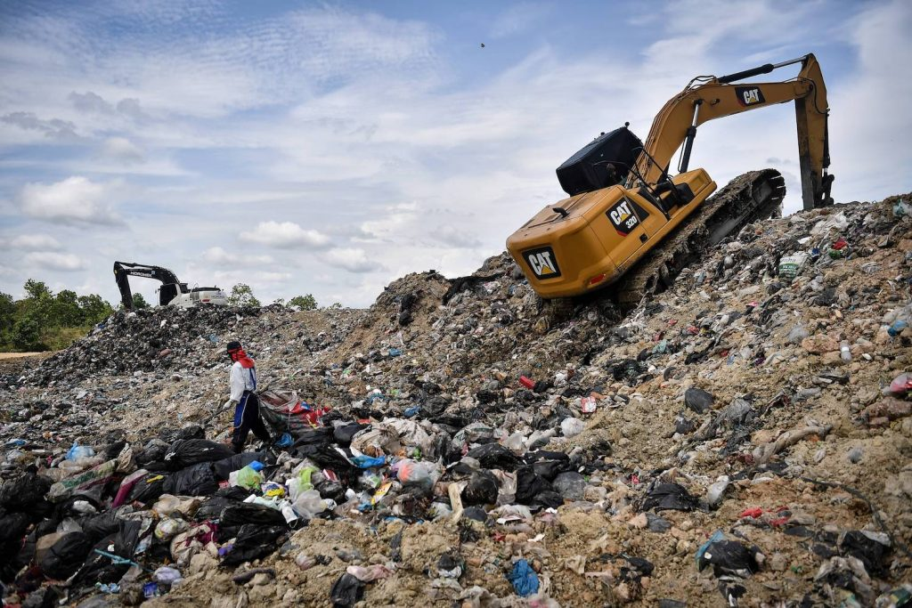 Pictured is a landfill with bulldozers climbing the side, mulching leaves can help reduce landfill waste