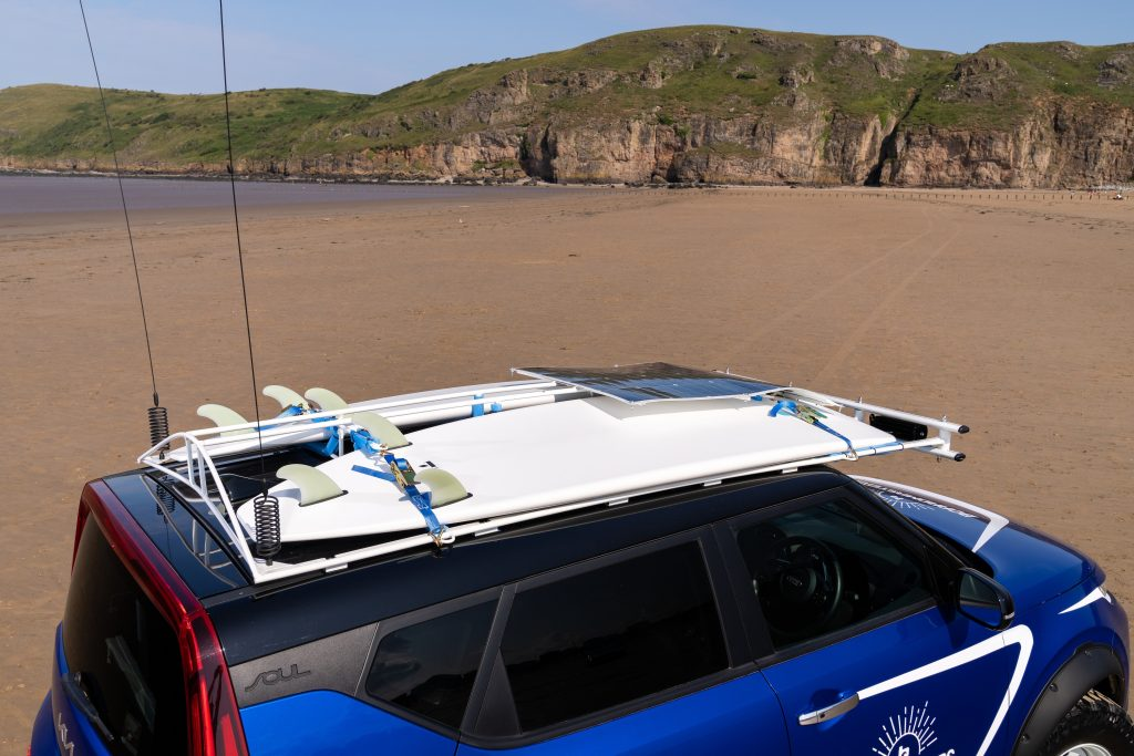 Two surfboards ratchet-strapped to the roof of the Beach EV