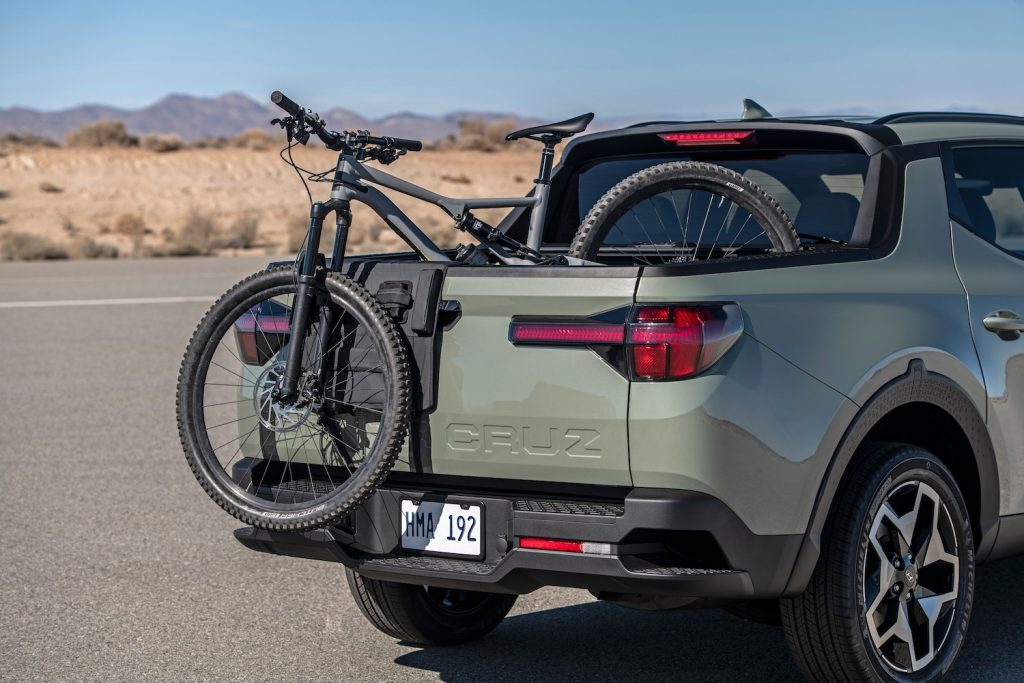 This is a promotional photo of a light green Hyundai Santa Cruz with a bicycle in its truck bed. The Santa Cruz is a crossover truck with the smallest truck bed available.