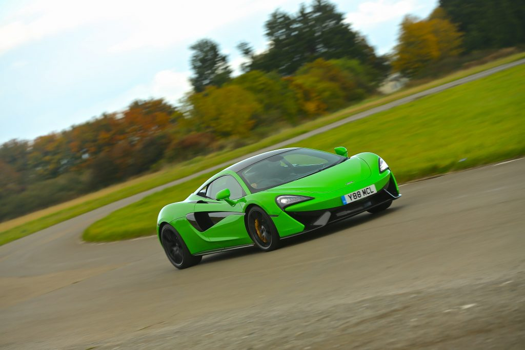 A green Mclaren 570s on a track in the UK