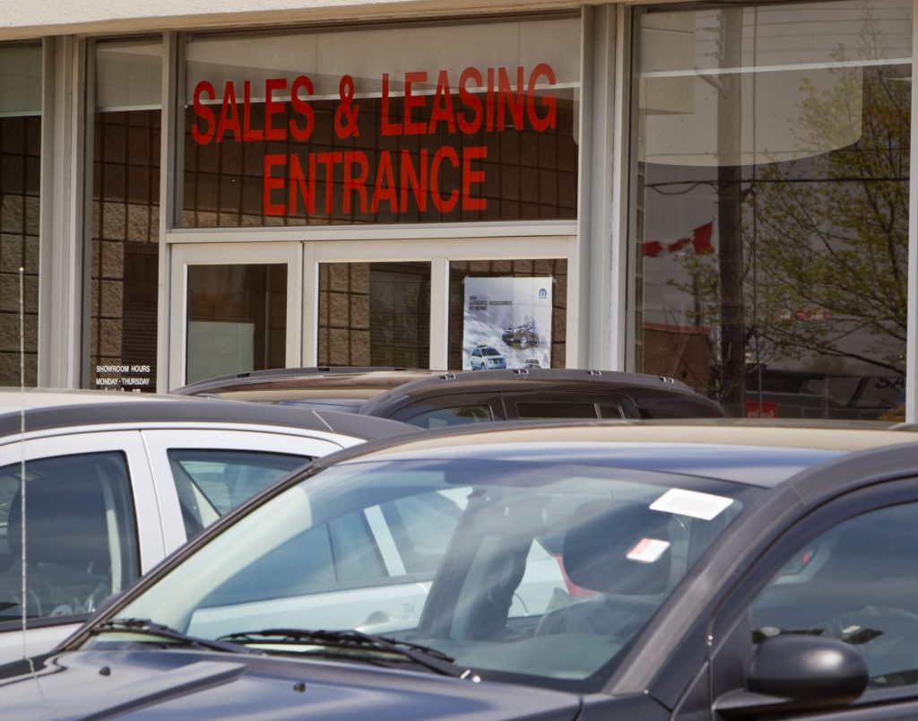 Sales and Leasing Entrance is written above a door with cars sitting in front of it.