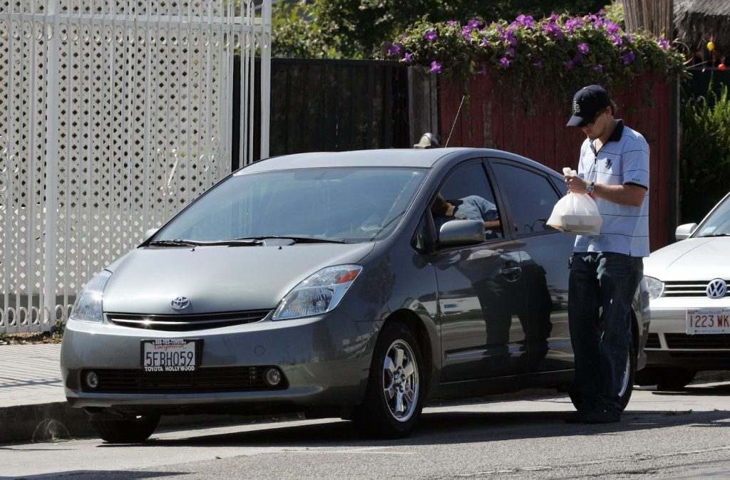 Leonardo DiCaprio getting into his Toyota Prius, one of the cheapest cars owned by one of the world's richest celebrities