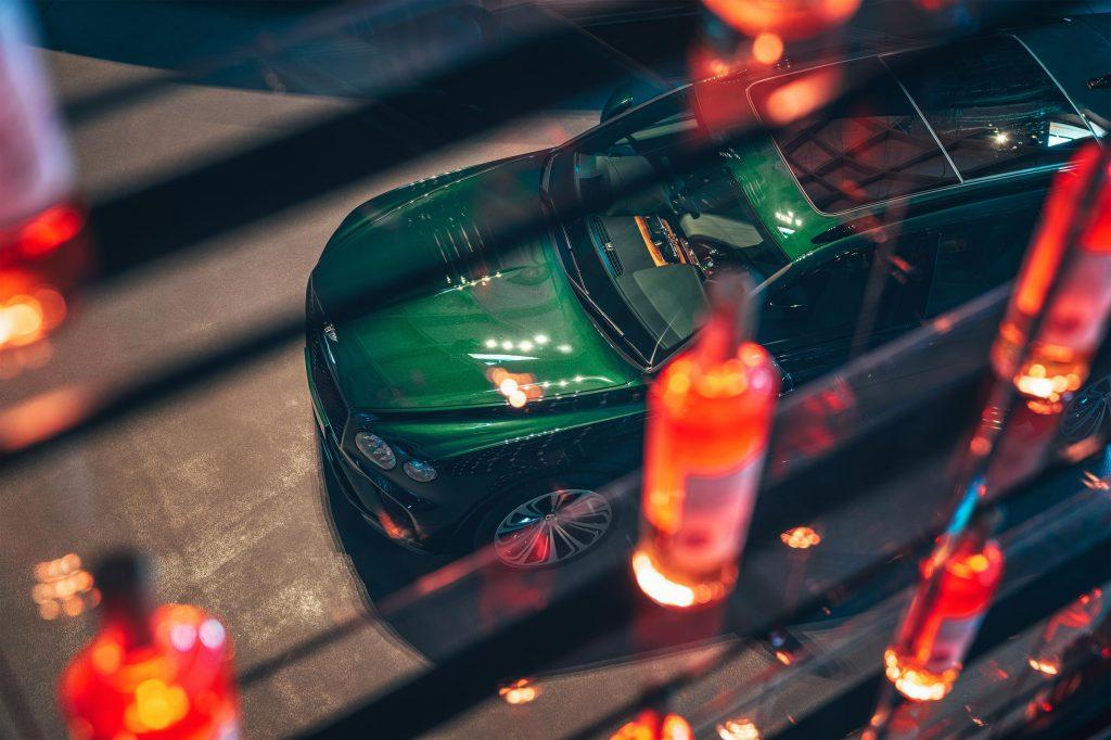 A green Bentayga Hybrid photographed through lights at night