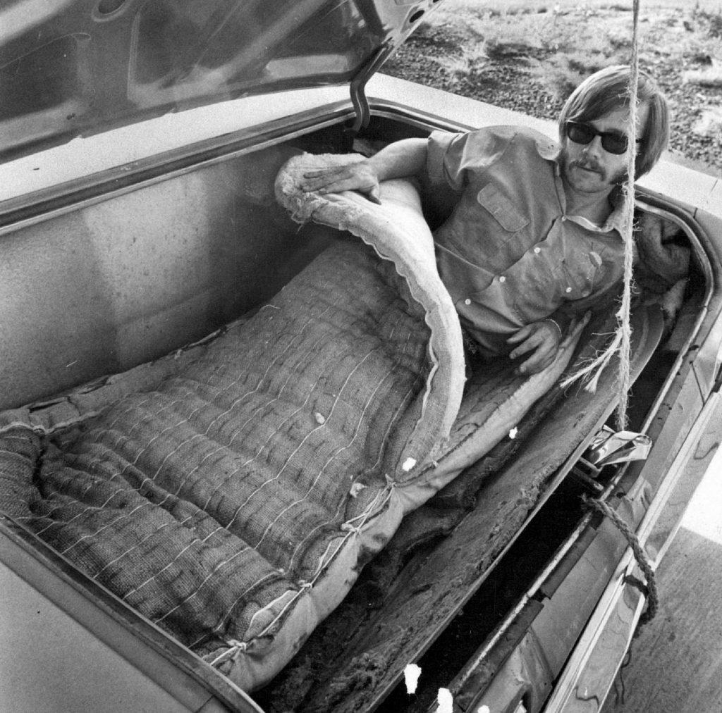 Man preparing to sleep in trunk of car