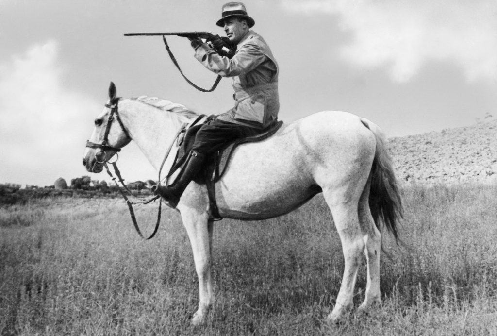 Man With Shotgun Riding A Horse
