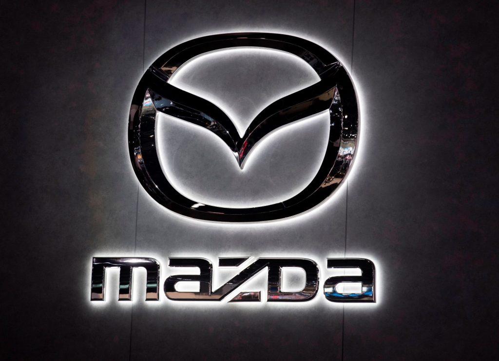 An illuminated chrome Mazda sign with Mazda written underneath the logo on black background.