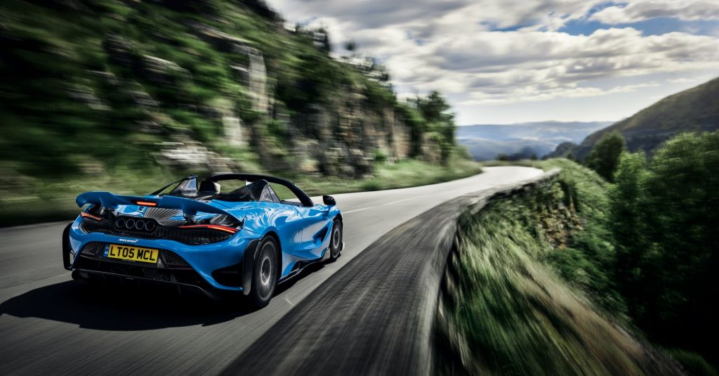 The McLaren 765LT Spider in blue driving down a country highway near cliffs