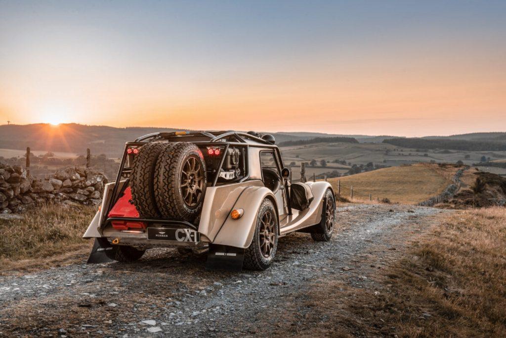 The rear 3/4 view of a tan Morgan Plus Four CX-T on a rocky plains trail